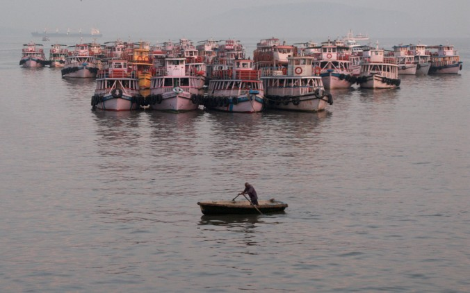 A man rows his boat across the harbor in Mumbai as dawn breaks.