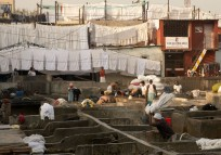 Mumbai's Dhobi Ghat is the world's largest open-air laundry. The system is corporate in its efficiency. Like colors are washed together. All white sheets here. The system includes pickup and delivery people, sorters, washers, irons and repackaging the clean clothes.