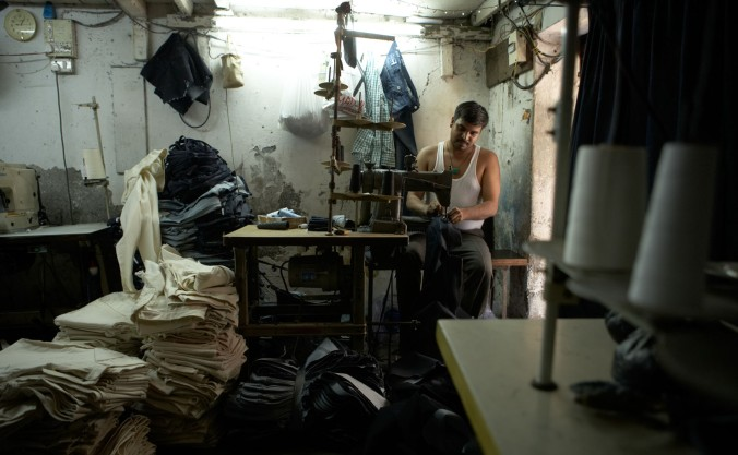 In this denim factory in the Dharavi slum, this man is sewing panels together to create jeans.