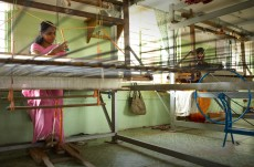 Weaving is a core part of the Women's Co-op. Rabia has been operating one FFC loom for seven years. In the Women's Co-op a wheel called a Charkha is used to spin thread from damaged cocoons in to a nubby silk thread, which is dyed and woven into products.