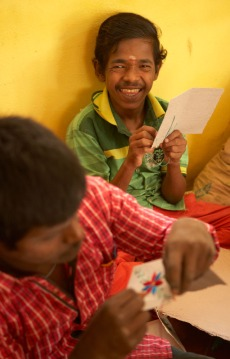 Papermaking has its own division of the Families For Children Training Center. Some residents tear the newspaper to make the recycled paper. Others, like these young men are responsible for embroidering designs on the cards.