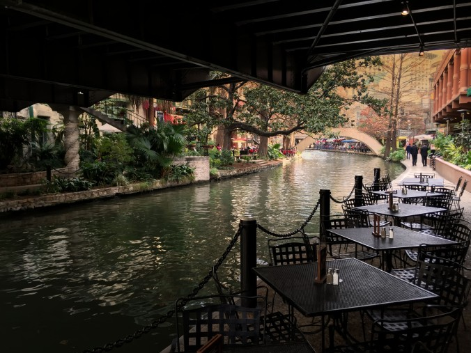 Tables along the San Antonio River Walk set for lunch. This eating area is below a bridge carrying traffic through the downtown. The River Walk has a charming, frozen-in-time atmosphere. It is the centerpiece of yearly San Antonio festivals including Fiesta San Antonio when flowery floats drift along the river.
