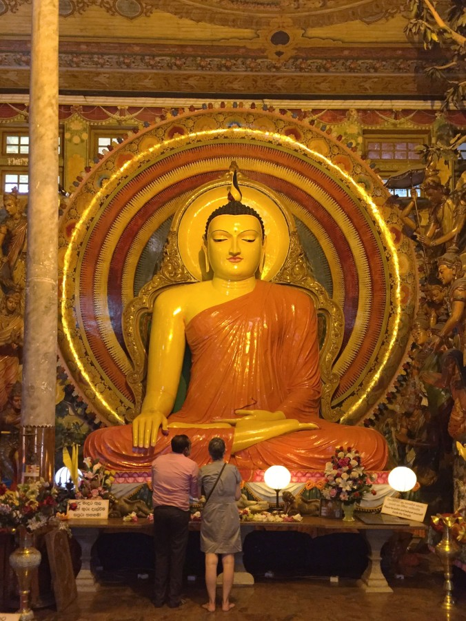 At the Gangaramaya Buddhist Temple, Raschman offers a blessing to Buddha on my behalf, asking for a safe journey for me and MacGyver in Sri Lanka.